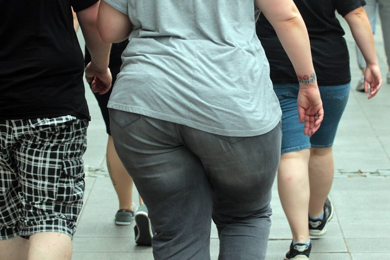 A woman is wearing tight clothes which make her look bigger.