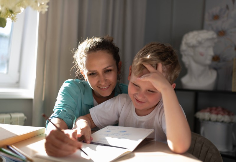 A babysitter helps a kid doing his homework.