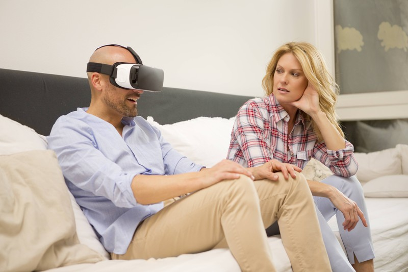 A blonde woman is irritated by her partner who is wearing a virtual reality headset.