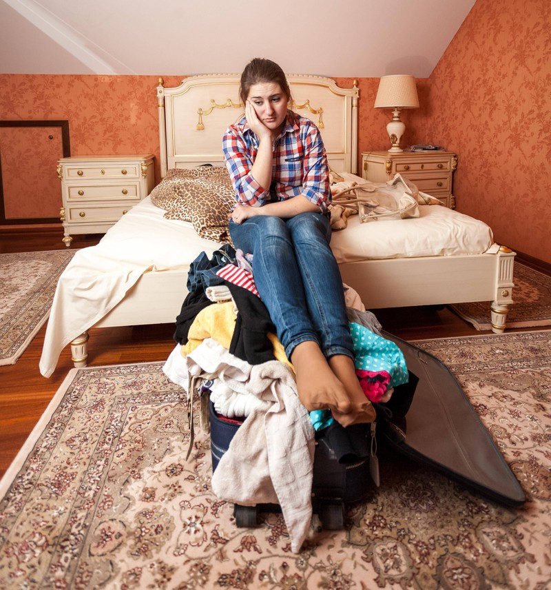 Woman packs her things to leave her husband.