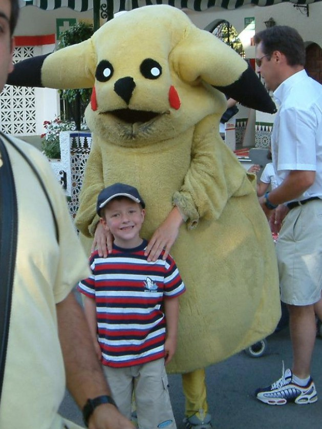 A kid poses with a creepy looking Pikachu.