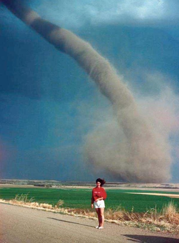 A woman thought it's a good idea to take a picture with a tornado.