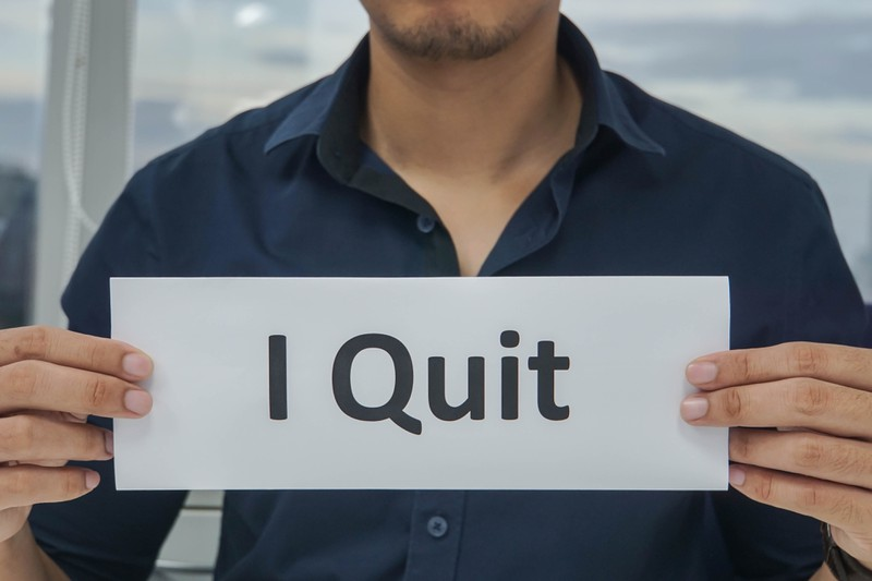 "A person holding a sign reading ""I Quit""."