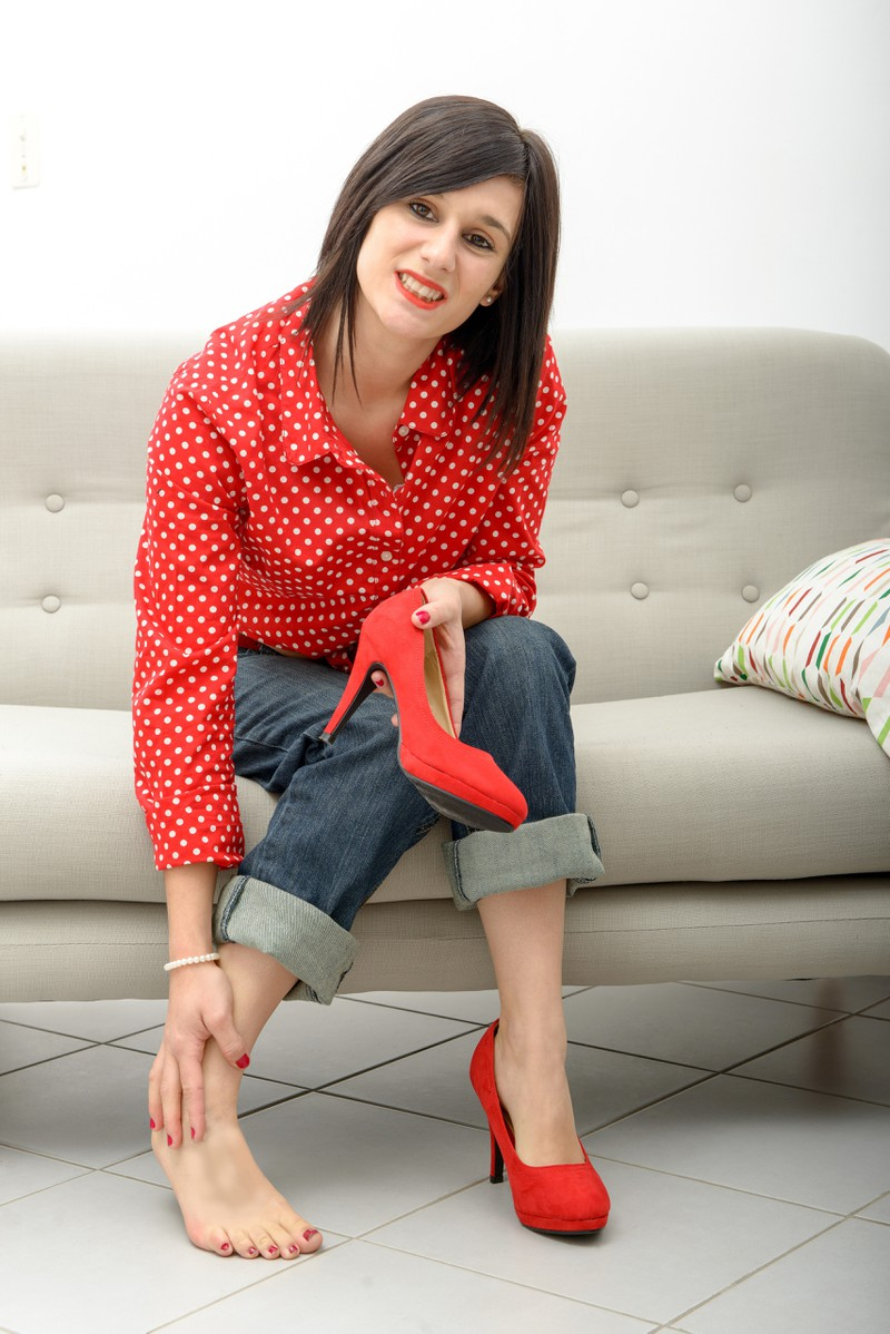 The young woman's feet are in pain because she wore her heels on the wrong feet.