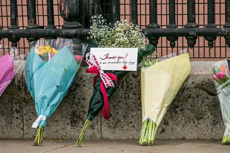 Mourners place flowers and kind messages in front of Buckingham Palace.