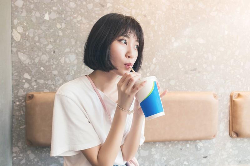 A woman enjoys a Coke light.
