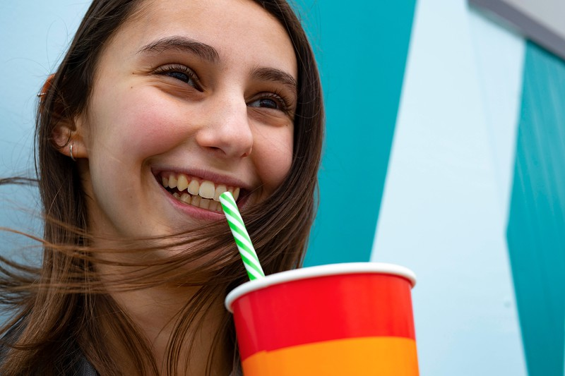 This woman is happy because she just had a sugary soft drink.