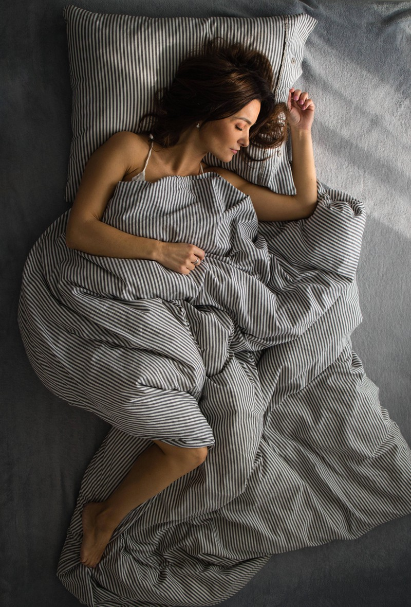 The woman doesn't want to sleep without her blanket, even though it's hot in her apartment.