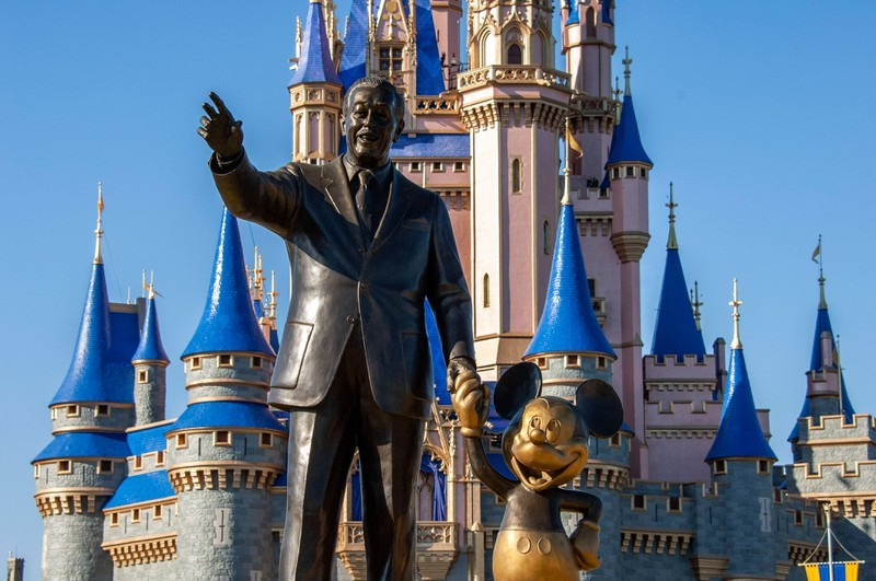 Walt Disney statue with castle and Mickey Mouse