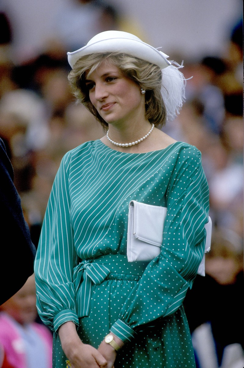 Princess Diana stuns in a beautiful dress, a pearl necklace and pearl earrings.
